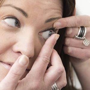 Female inserting soft contact lens.
